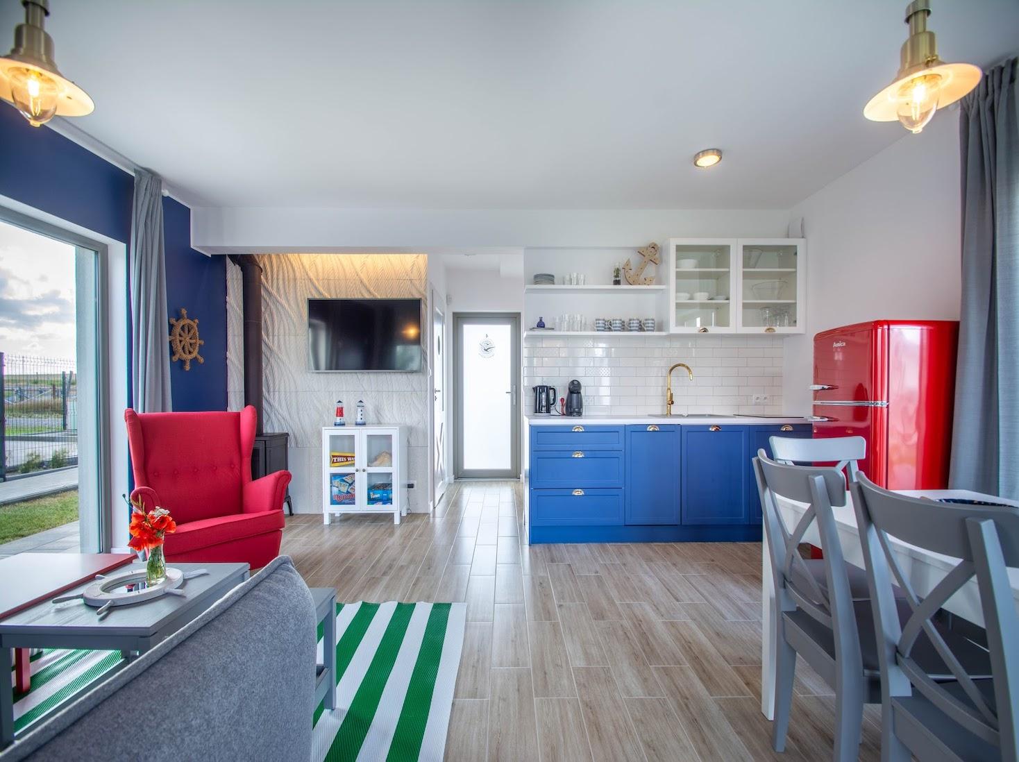 Domek letniskowy salon czerwony fotel granatowa kuchnia