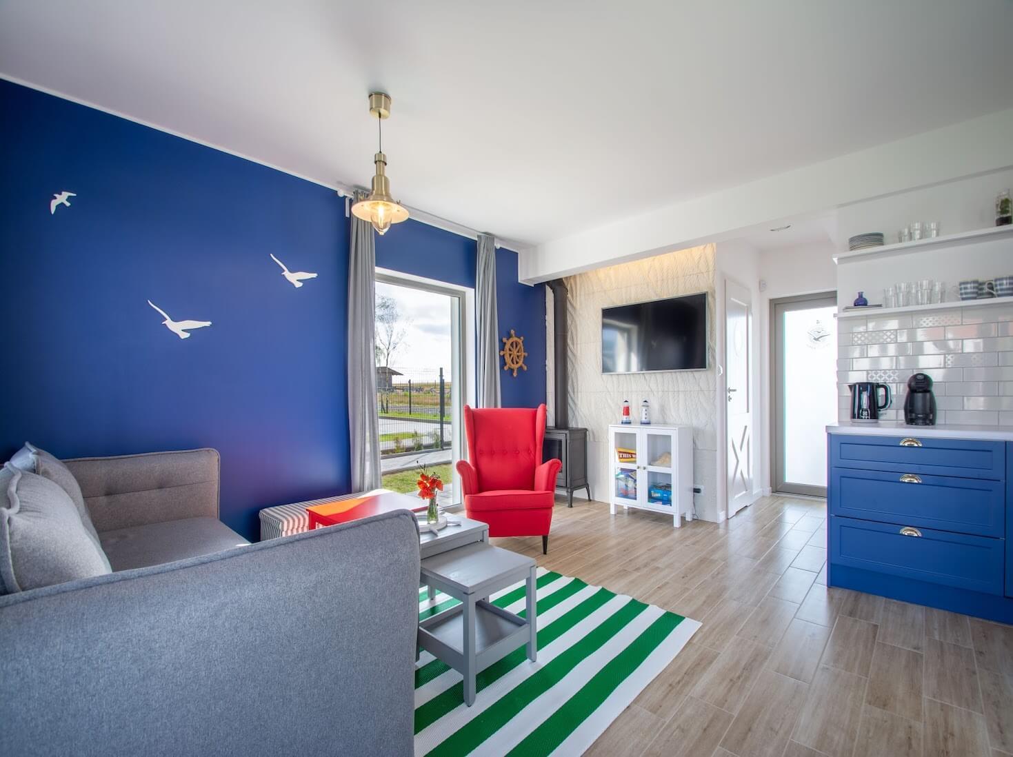granatowa ściana, dekoracje ścienne, mewy na ścianie, dywan w pasy, pasy, czerwony fotel, fotel uszak